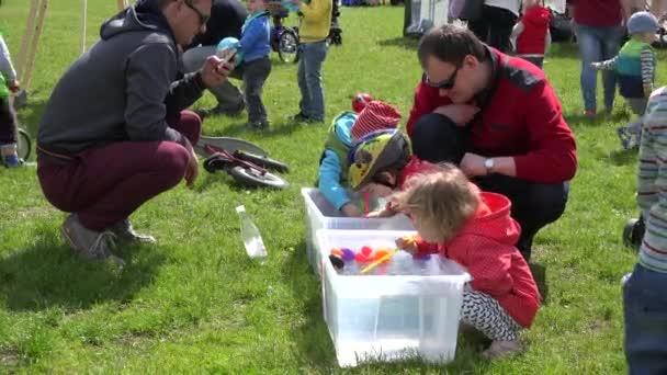 Jungen und Mädchen spielen Entenrennen im kleinen Wasserbecken mit Stroh. 4k