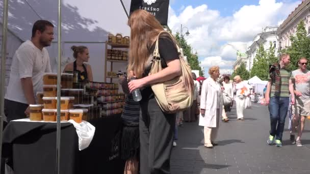 Beekeepers sell natural honey in outdoor market and people walk. 4K