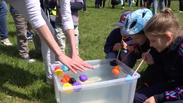 Kinder mit Stroh spielen Entenrennen im Plastikwasserbecken. 4k