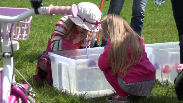 Kinder spielen Entenrennen Spiel im Wasserbecken mit Stroh. 4k