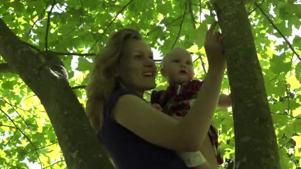 mother with little daughter play in green park under tree. 4K