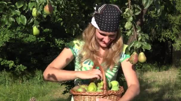 smiling gardener woman holding basket of ripe harvested pears throw ripe fruit toward camera. 4K