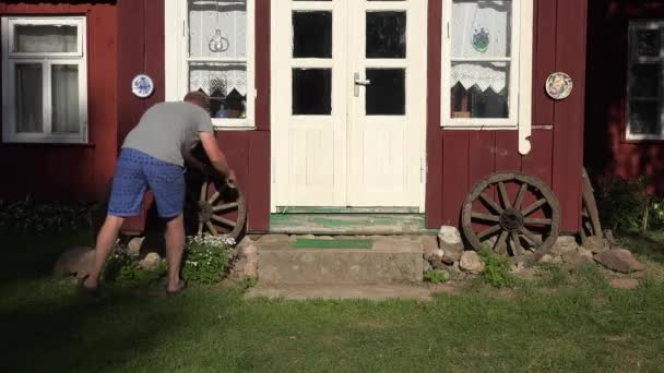man in shorts roll retro cart wheel near country wooden house. 4K