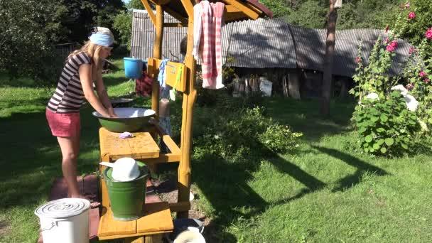 arme, einsame Bäuerin, die ihre Wäsche von Hand in einer Metallschale im Hof wäscht. 4k