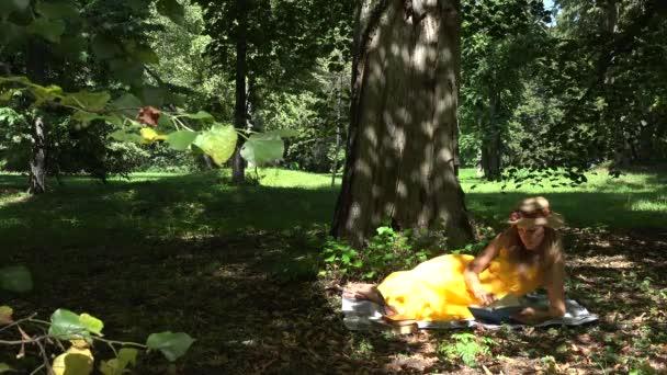 Student girl preparing for final exam reading book in nature. 4K