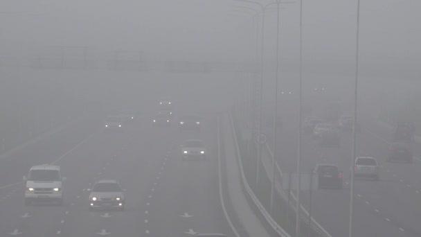 Blurred background of dense autumn fog on city highway road. 4K