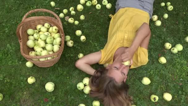 Elég fiatal Kertész lány feküdt füvön közelében kosár tele gyümölcsöt és kicsit íze Alma gyümölcsöt. 4k