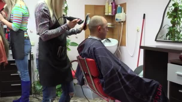 Barber cut man hair with clipper and hair stylist dye female hair. Zoom out. 4K