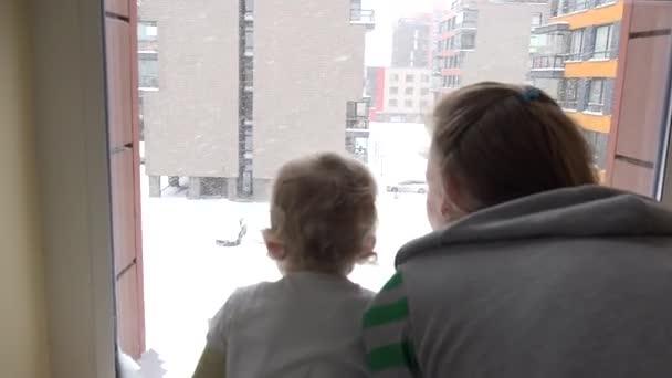 Matka a dítě si sníh padá vyhlížející z okna v místnosti bytu domu. 4k