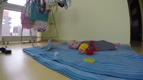 Aufräumraum, Kind liegt auf blauer Matte. Hausstaubsaugen. 4k