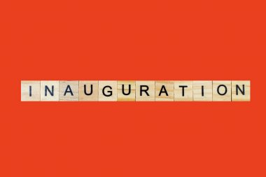 Inauguration . English word on red background composed from letters on wooden cubes. Learning english concept
