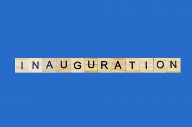 Inauguration . English word on blue background composed from letters on wooden cubes. Learning english concept