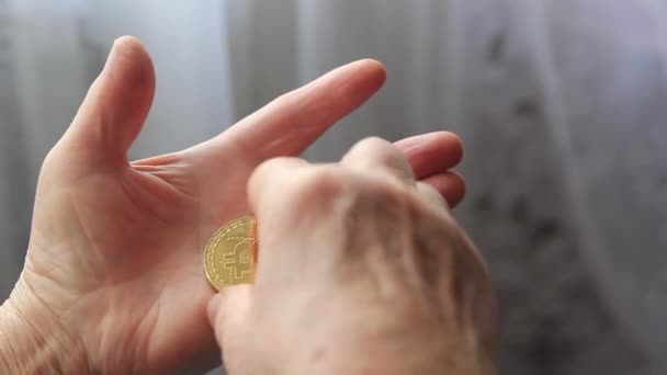 The female hands of an elderly woman are holding a bitcoin coin close-up