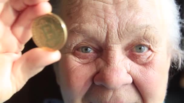An elderly woman, a grandmother, is holding a bitcoin coin in her hands and leans it to her eye.