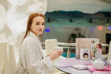 close up photo of a sexy beautiful reddish woman in white bath gown drinking tea in the fito bar of a spa centre