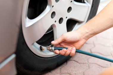 Man is controlling the tire pressure of car