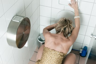 Woman throwing up in the toilet