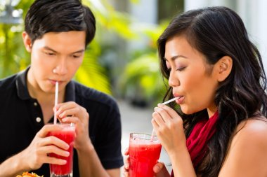 Asian man and woman in restaurant are drinking Cocktails stock vector
