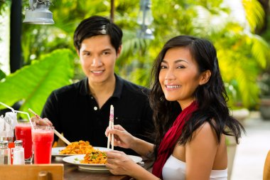 Asian man and woman in restaurant eating their food with chopsticks stock vector