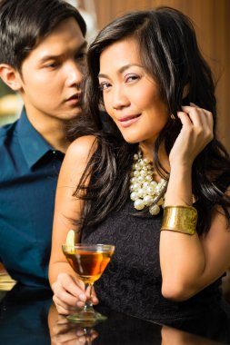 Asian man and woman at bar with cocktails