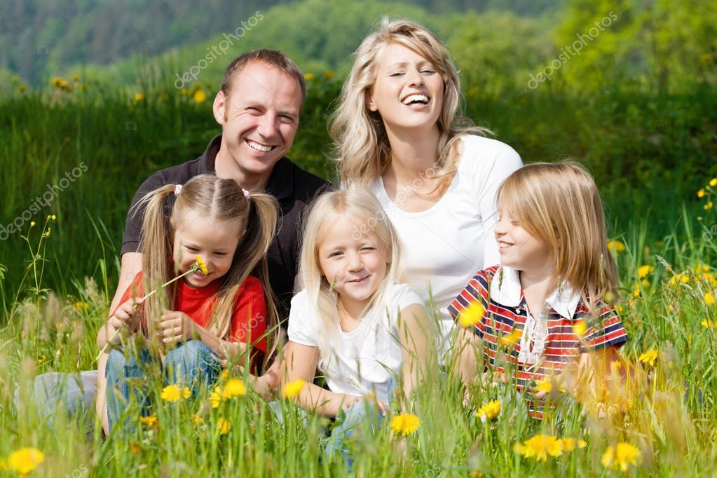 Happy family in summer on meadow