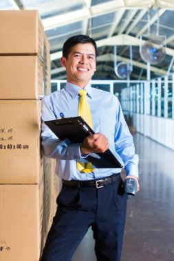 Young Indonesian man in a suit with a bar code scanner in a Asian warehouse of forwarding or logistics company stock vector