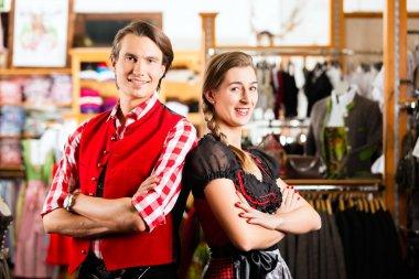 Couple is trying Dirndl or Lederhosen in a shop