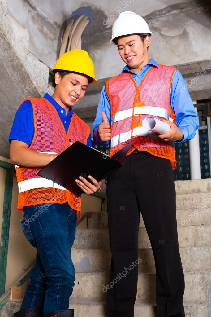 Asian supervisor and worker on building site
