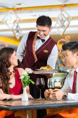 waiter serving dinner in elegant restaurant