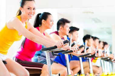 people in spinning bike training at fitness gym