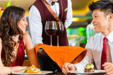 Waiter serving Chinese couple wine