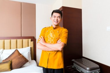Chinese porter bringing suitcase to hotel room