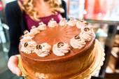Ženské baker prezentující dort v cukrovinkách