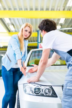 Customer and car painter in auto workshop