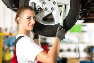 Female car mechanic working on jacked auto