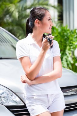 woman showing key of new car