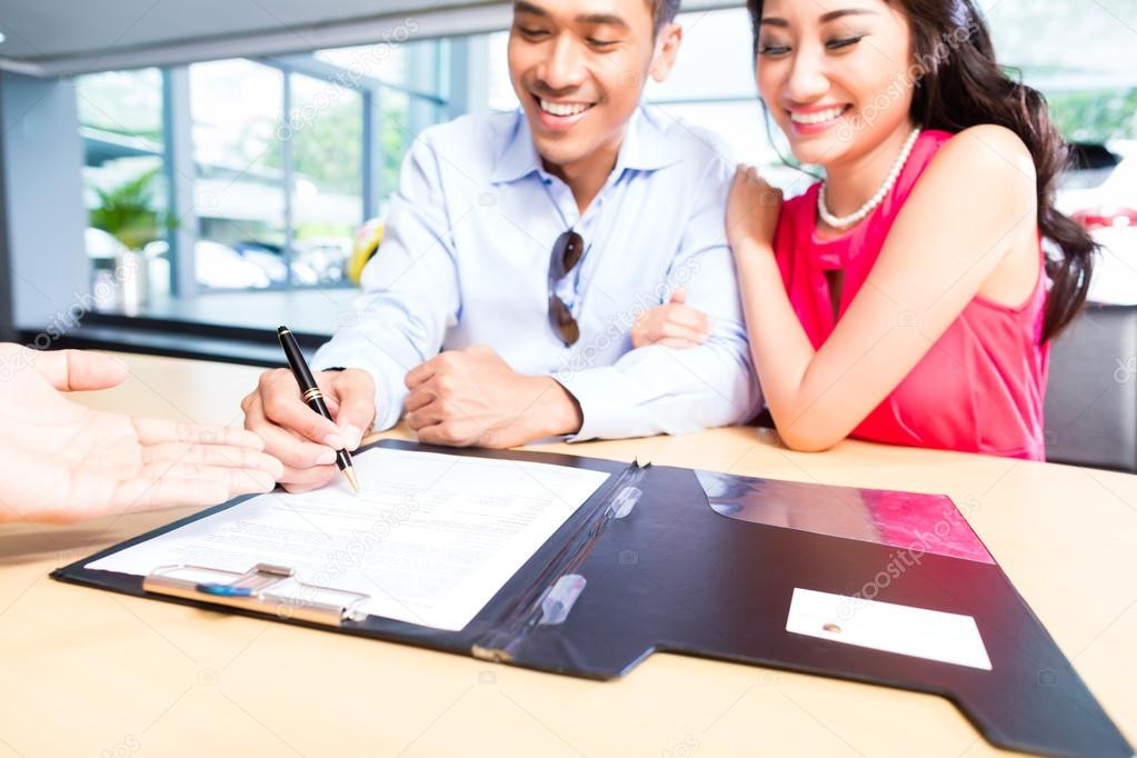 couple signing sales contract for car at dealership stock photo