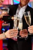 Lidé s champagner v baru