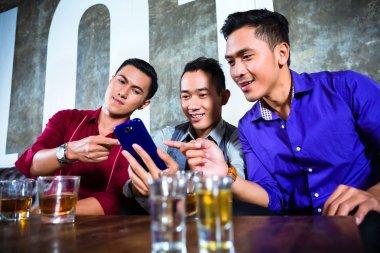 Asian friends drinking shots in nightclub