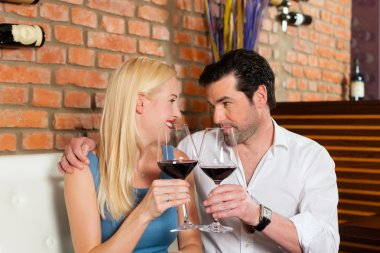 Attractive young couple drinking red wine in restaurant or bar, it might be the first date stock vector