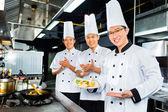 Fotografia Asian Chef nella cucina del ristorante hotel