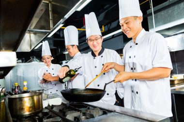 Asian Chefs in restaurant kitchen cooking