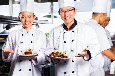 Asian Chef in restaurant kitchen cooking