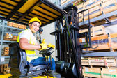 Photo fork lift truck driver lifting pallet in storage