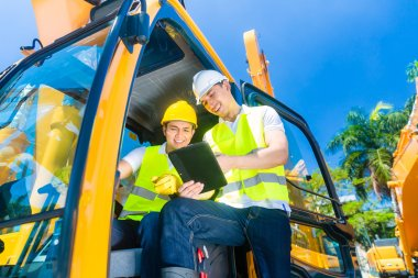 construction driver discussing with engineer blueprints