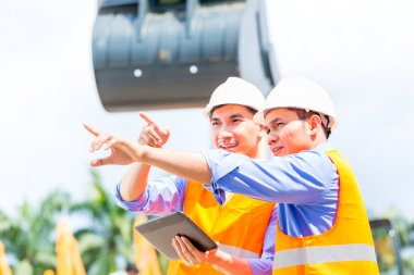 engineer discussing plans on construction site