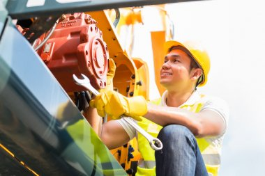 Asian mechanic repairing construction vehicle