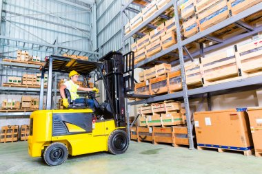 fork lift truck driver lifting pallet in storage