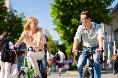 Urban couple riding bike in city