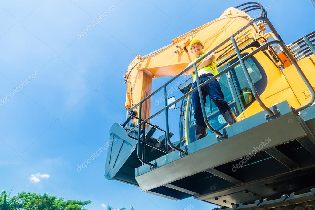 Asian construction worker on shovel excavator